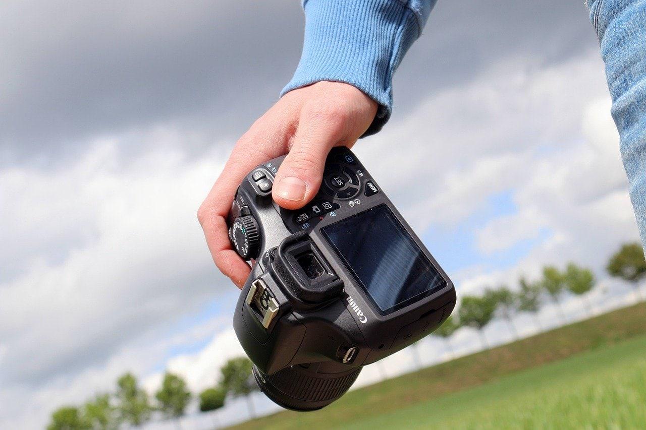 hand houdt camera vast in natuuromgeving